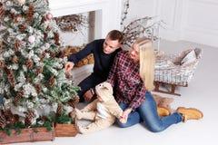 lycklig julfamilj Föräldrarna och behandla som ett barnsammanträdet på golvet och le Arkivbilder