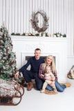lycklig julfamilj Föräldrarna och behandla som ett barnsammanträdet på golvet och le Royaltyfria Bilder