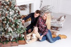 lycklig julfamilj Föräldrarna och behandla som ett barnsammanträdet på golvet och le Fotografering för Bildbyråer