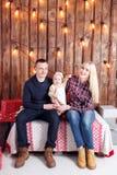 lycklig julfamilj Föräldrarna och behandla som ett barnsammanträdet vägg av den träplankor och girlanden Fotografering för Bildbyråer