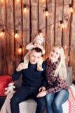 lycklig julfamilj Föräldrarna och behandla som ett barnsammanträdet vägg av den träplankor och girlanden Royaltyfria Foton