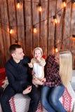 lycklig julfamilj Föräldrarna och behandla som ett barnsammanträdet vägg av den träplankor och girlanden Arkivbilder