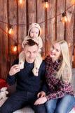 lycklig julfamilj Föräldrarna och behandla som ett barnsammanträdet vägg av den träplankor och girlanden Royaltyfria Bilder