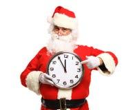 Lycklig jultomten i glasögon som pekar på klockan som visar fem minuter Fotografering för Bildbyråer