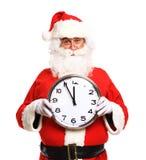 Lycklig jultomten i glasögon som pekar på klockan som visar fem minuter Arkivbilder