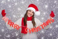 Lycklig jultomtenflicka som visar tecknet för glad jul Royaltyfri Bild