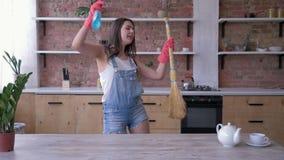 Lycklig köklokalvård, ståenden av hemmafrun för den unga kvinnan i jeanoveraller och handskar dansar lyckligt med kvasten och
