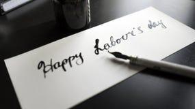 Lycklig kalligrafi för dag för arbete` s och lattering vykort Vänstersidasikt med calligraphpennan Royaltyfria Foton