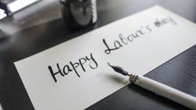 Lycklig kalligrafi för dag för arbete` s och lattering vykort Vänstersidasikt med calligraphpennan Arkivbilder