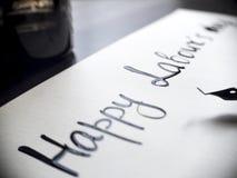Lycklig kalligrafi för dag för arbete` s och lattering vykort Vänstersidasikt med calligraphpennan Fotografering för Bildbyråer