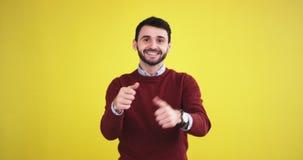 Lycklig karismatisk ung man i studion med en gul bakgrundsvägg som ser rak till le för kamera som är stort och lager videofilmer