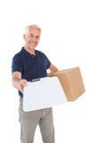 Lycklig kartong och skrivplatta för leveransman hållande Royaltyfri Foto