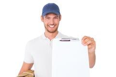 Lycklig kartong och skrivplatta för leveransman hållande Arkivfoto