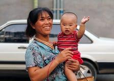 Lycklig kinesisk kvinna med en behandla som ett barn i henne armar Arkivbilder
