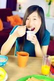 Lycklig kinesisk kvinna som äter den vita yoghurten royaltyfri foto