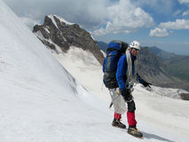 Lycklig klättrare på snöalpinistrutten arkivfoto
