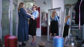 Lycklig klient som försöker på den färdiga klänningen i atelier lager videofilmer