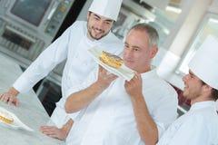Lycklig kock som upp ser maträtten Arkivbild