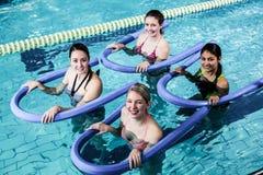 Lycklig konditiongrupp som gör aquaaerobics med skumrullar Royaltyfri Fotografi