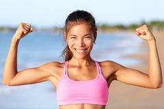 Lycklig konditionkvinna som böjer muskler på stranden - Arkivbilder