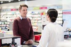 Lycklig kund som lyssnar till rekommendationerna av en pålitlig apotekare arkivbild