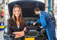 Lycklig kund som väntar på en mekaniker att fixa hennes bil royaltyfri bild