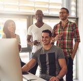 Lycklig kvartett av unga vuxna människor på skrivbordet arkivfoton