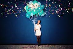 Lycklig kvinna, ballonger och konfettier på blått baner Arkivbild