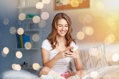 Lycklig kvinna eller flicka med smartphonen i säng hemma royaltyfria bilder