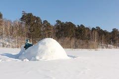 Lycklig kvinna ett rött omslag som bygger en igloo på en snöglänta i vintern, Sibirien, Ryssland royaltyfri foto