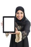 Lycklig kvinna för arabiska saudieremirater som visar en app i en minnestavlaskärm royaltyfri bild