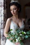 Lycklig kvinna för härlig delikat sexig brud med en krona på hennes huvud vid fönstret med en stor bröllopbukett i en lyxig vit Royaltyfria Bilder
