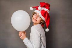 Lycklig kvinna för jul som rymmer en ballong som drömmer om något Royaltyfri Foto