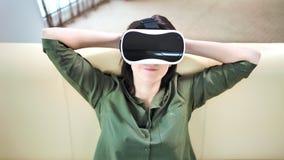 Lycklig kvinna för medelskott som ler och kopplar av den bärande virtuell verklighethörlurar med mikrofon arkivfilmer