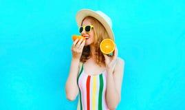 Lycklig kvinna f?r sommarst?ende som rymmer i hennes h?nder och ?ter skivor av orange frukt i sugr?rhatt p? f?rgrika bl?tt royaltyfri bild