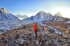 Lycklig kvinna för fotvandrare som trekking på det insnöat ett snöig berg Royaltyfri Bild