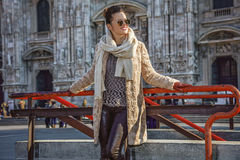 Lycklig kvinna framme av duomoen i Milan, Italien som åt sidan ser Arkivfoton