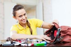 Lycklig kvinna funnit ting i handväska arkivfoto