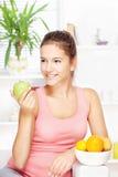 Lycklig kvinna hemma med frukter Royaltyfri Foto