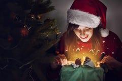 Lycklig kvinna i ask för gåva för santa hattöppning på ligh för julträd Fotografering för Bildbyråer