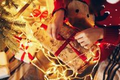 Lycklig kvinna i ask för gåva för santa hattöppning på ligh för julträd Royaltyfri Bild