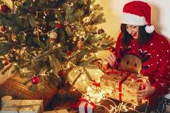 Lycklig kvinna i ask för gåva för santa hattöppning på ligh för julträd Arkivfoto