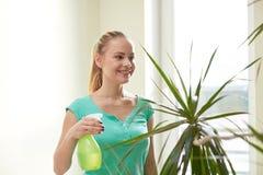 Lycklig kvinna, i att bespruta houseplants hemma Arkivfoto