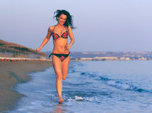 Lycklig kvinna i baddräktspring på stranden Royaltyfria Bilder