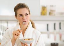 Lycklig kvinna i badrock som äter den sunda frukosten royaltyfria foton