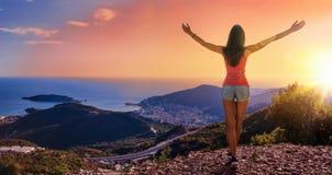 Lycklig kvinna i bergen som ser solnedgången royaltyfria foton