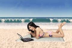 Lycklig kvinna i bikini med bärbara datorn på stranden arkivfoto