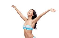 Lycklig kvinna i bikinibaddräkt med lyftta händer Arkivfoto