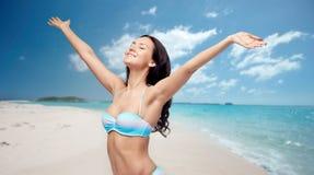 Lycklig kvinna i bikinibaddräkt med lyftta händer Arkivbilder