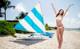 Lycklig kvinna i bikinibaddräktdans på stranden Arkivbild